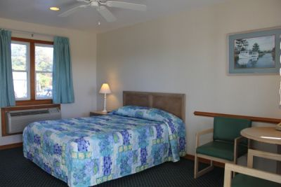 Poolside bedroom with queen bed at Pony Island Motel